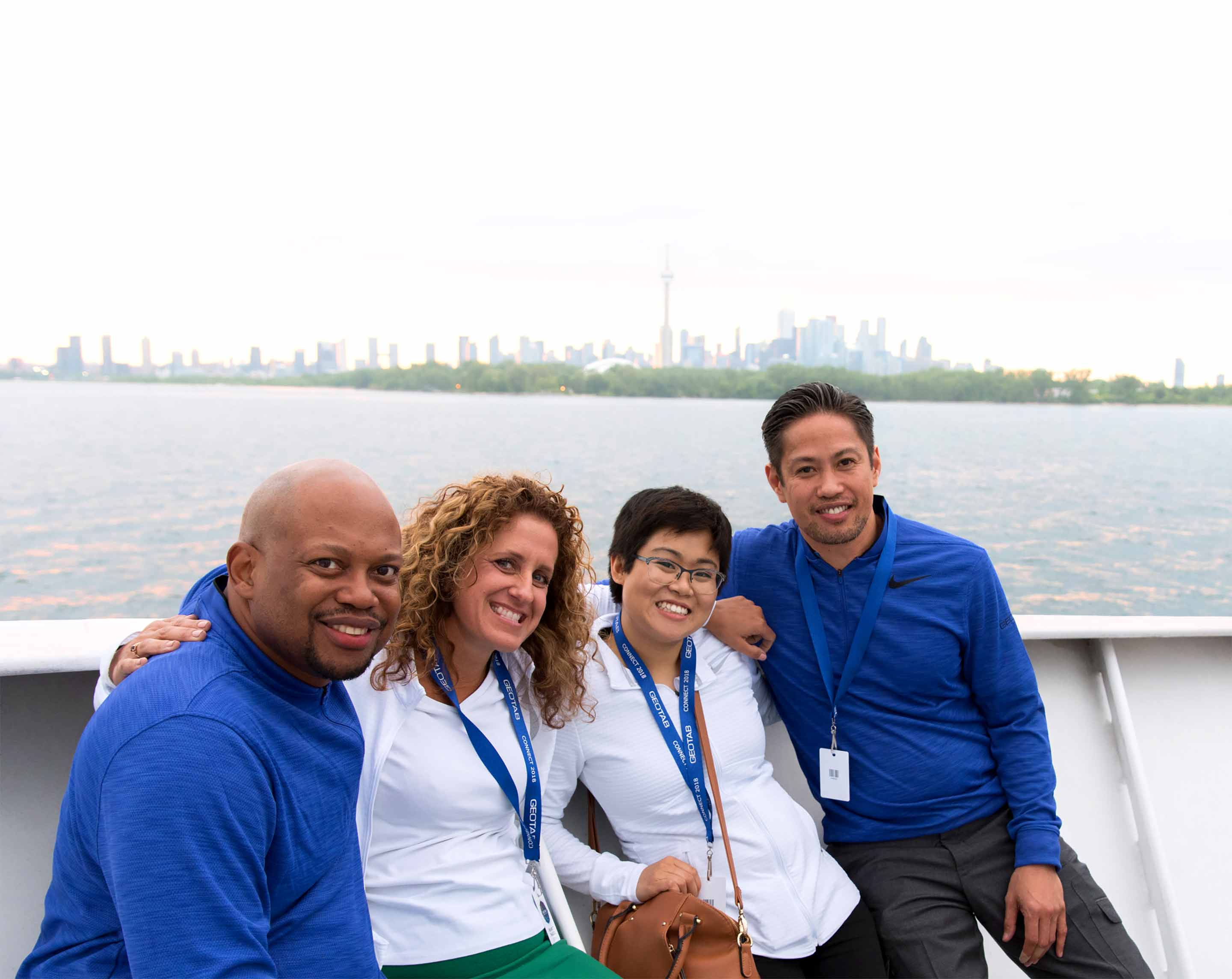 Four Geotab employees smiling while on a boat