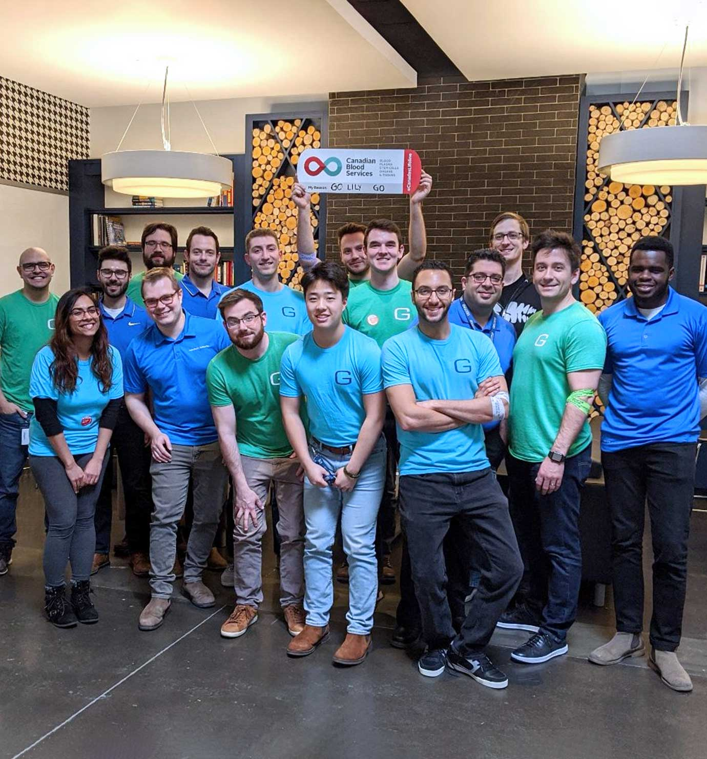 Group of Geotab employees sitting and standing in a truck loading dock