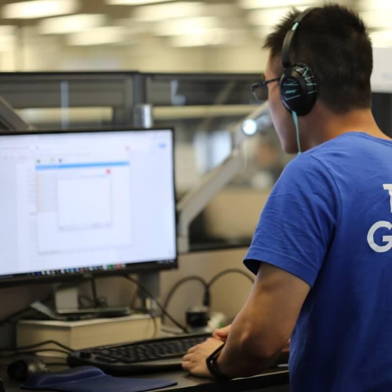 A Geotab employee at a desk wearing a Team Geotab inscribed blue shirt