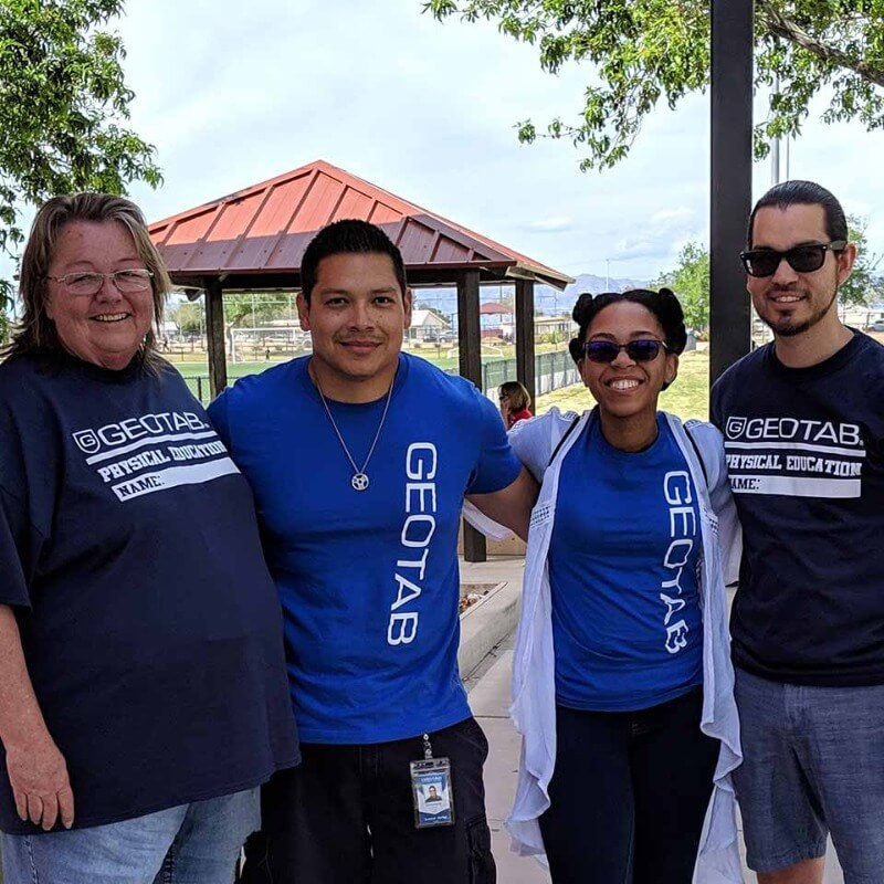 Four people smiling wearing Geotab tee shirts outside