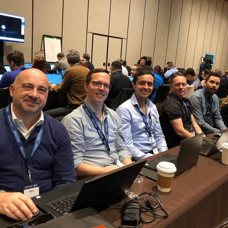 Five Geotab employees smiling sitting at a table in a row