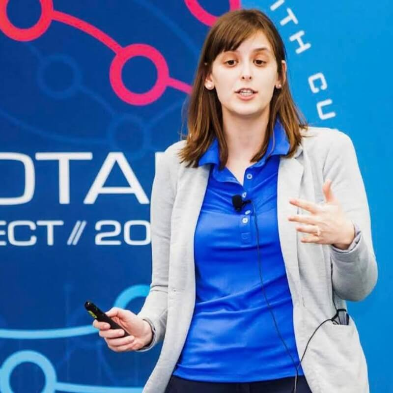 A woman with a blue shirt and sweater presenting in front of a crowd at Geotab Connect