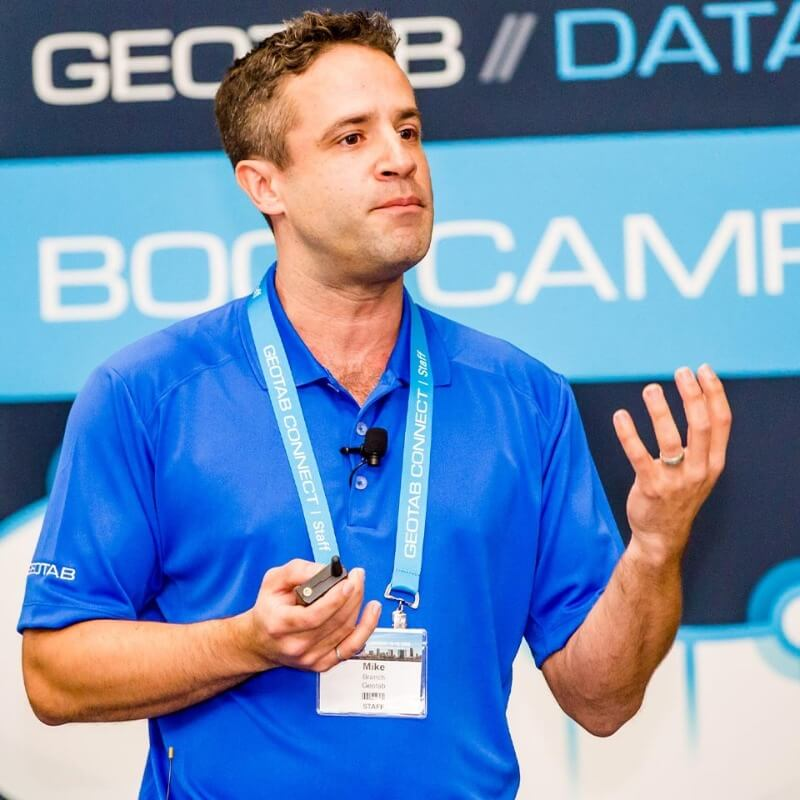A man in a blue shirt presenting at a Geotab bootcamp