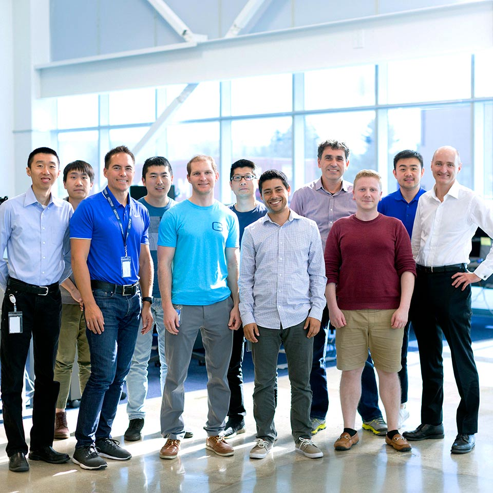 A group of Geotab employees standing together smiling.