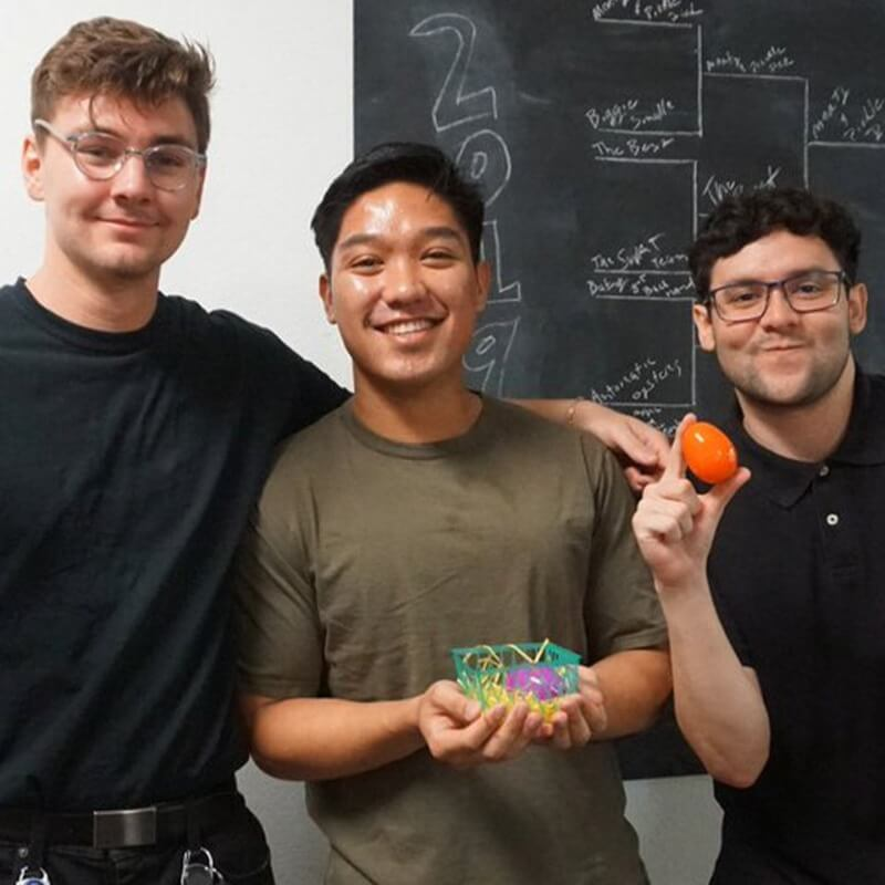 Three Geotab employees holding plastic easter eggs smiling
