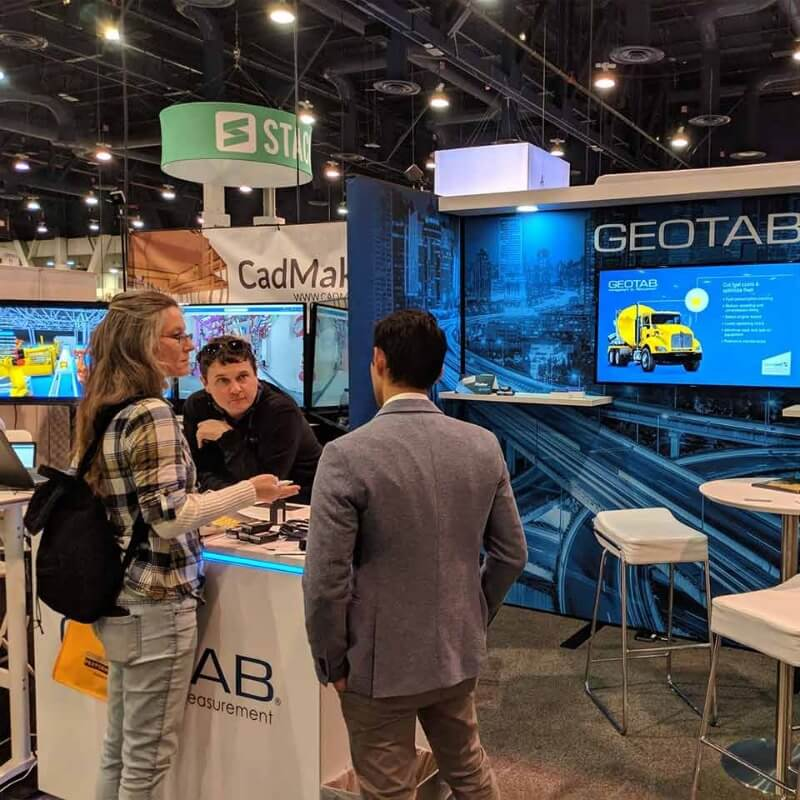 Three people talking at a Geotab booth at a convention