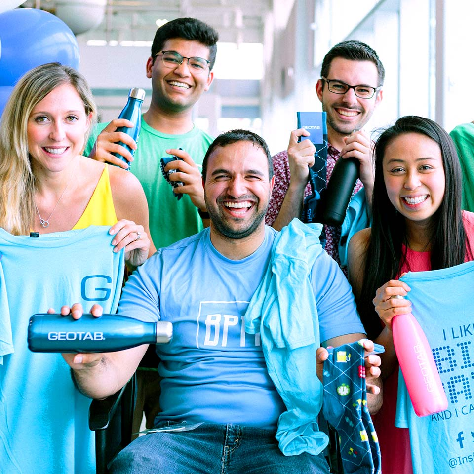 Six smiling Geotab employees holding Geotab t-shirts and water bottles.