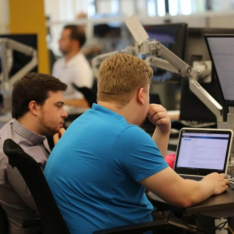 Two Geotab employees looking at a monitor at a desk