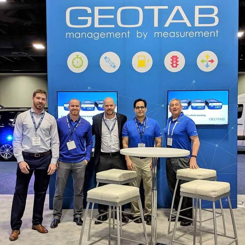 A group of Geotab employees standing in front of a Geotab booth at a convention
