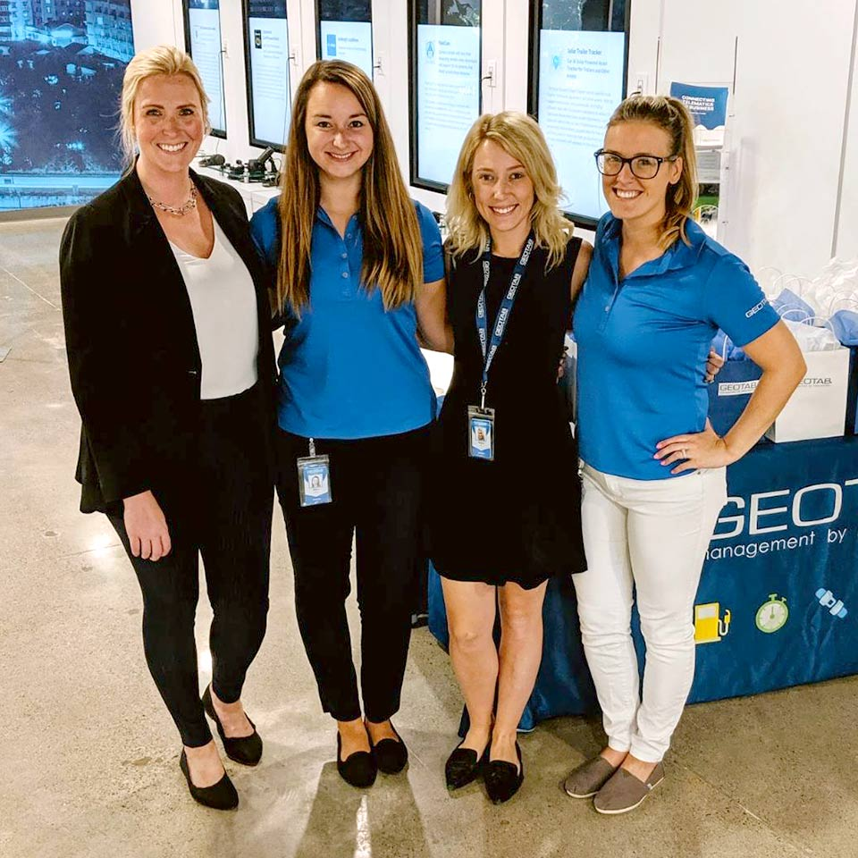 Three Geotab employees smiling and sitting outside cubicles