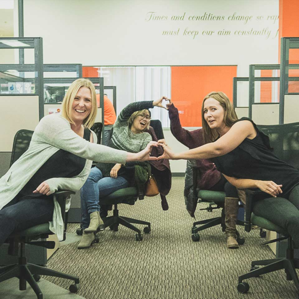 Four Geotab employees smiling together while sitting at their desks