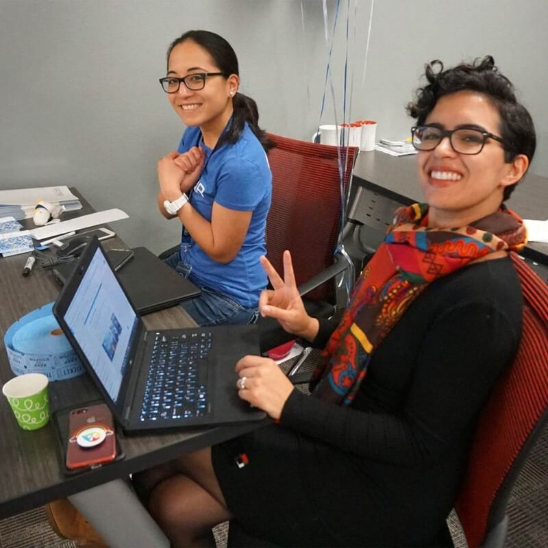 Two Geotab employees working at a desk on a laptop computer