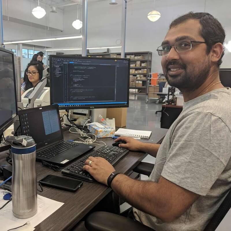 A brown haired man working at his desk on two monitors