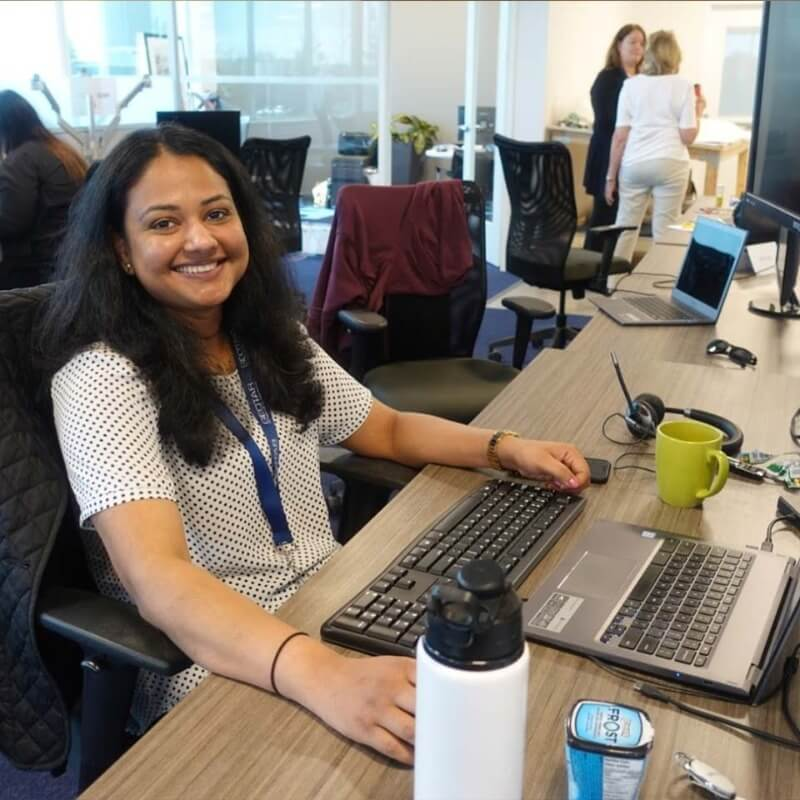 A woman with long black hair at her desk working and smiling
