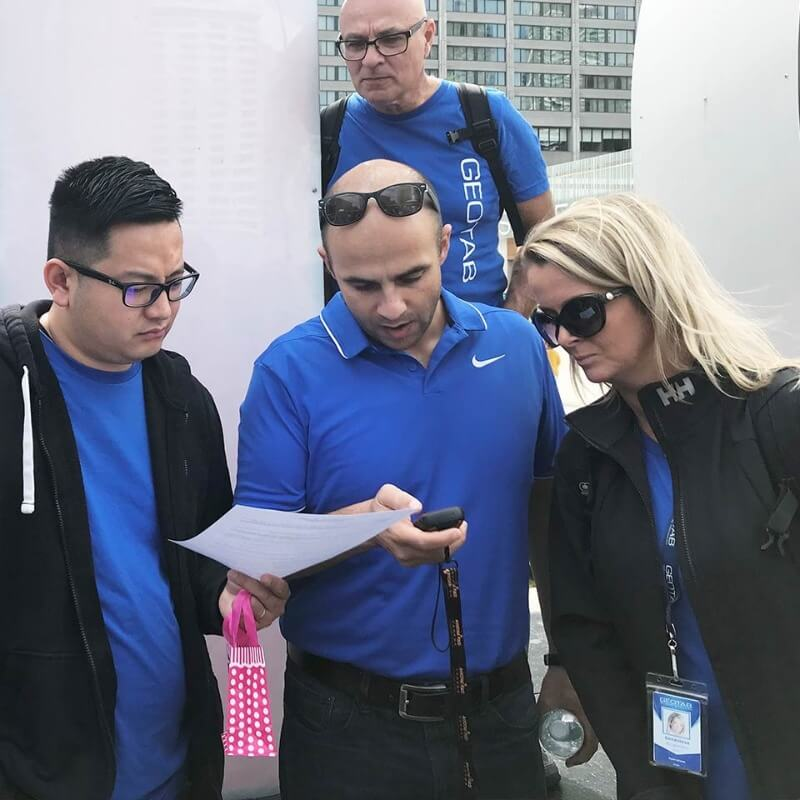A group of Geotab employees looking at papers and a phone while outside