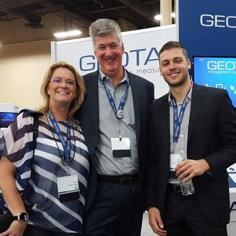 Three Geotab employees at a Geotab booth at a convention