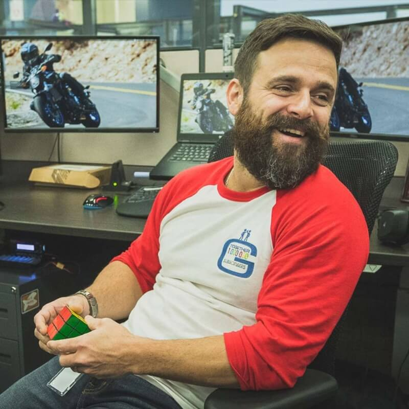 A bearded brown haired man sitting at a desk with a Rubix cube