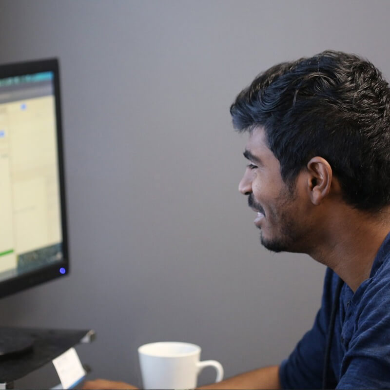 A dark brown haired man looking at computer smiling