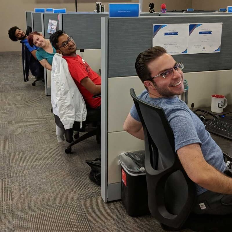 Four Geotab employees smiling at while at their cubicles